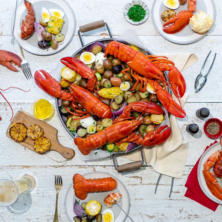Full Canadian Lobsters are pictured in a large pan with a variety of accompaniments. The pan is on a table set for four with charred lemons, herbs and spices.
