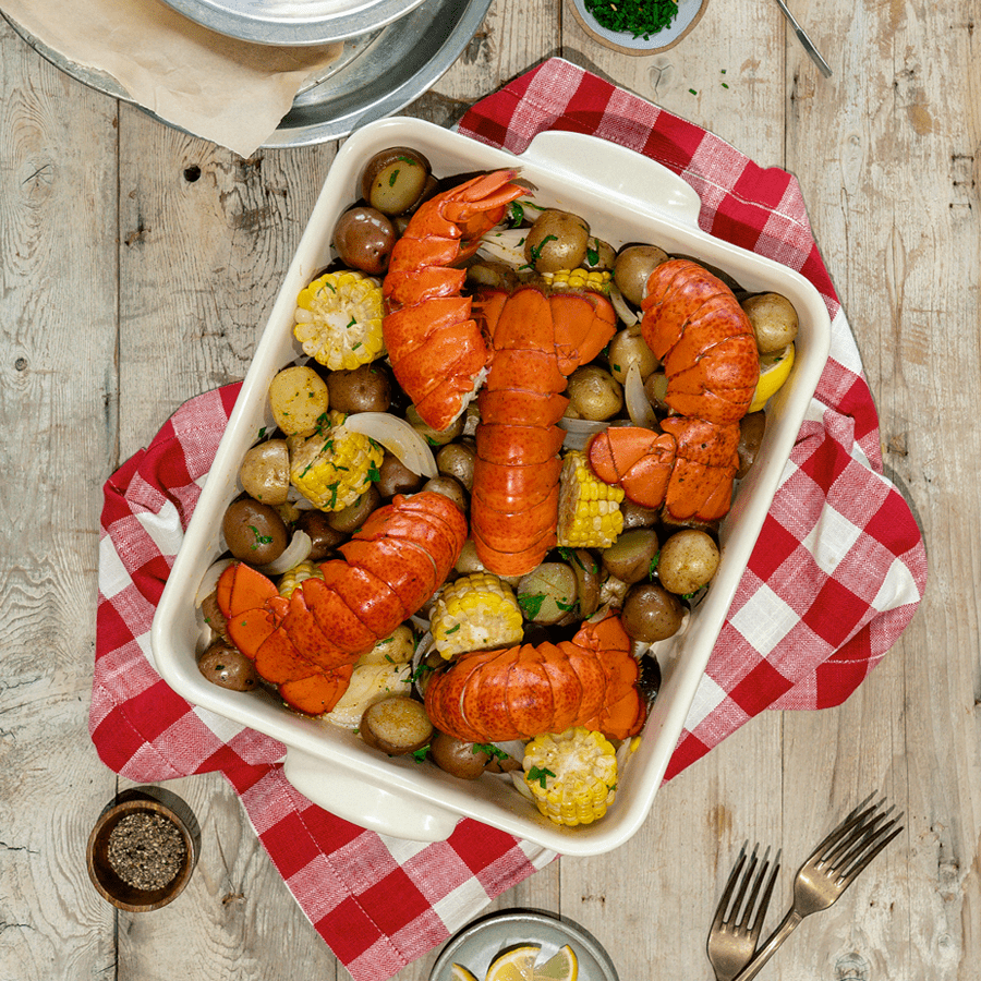 Canadian lobster tails in a baking pan with potatoes, corn and onions. The pan is on a rustic table on top of a gingham kitchen towel.